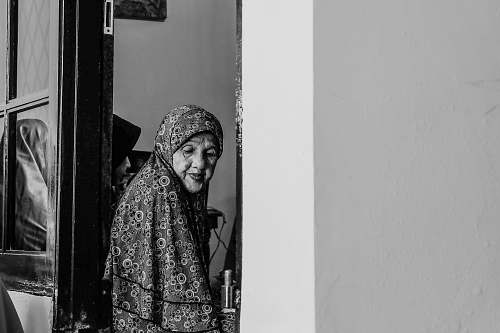 person grayscale photo of woman between doors black-and-white