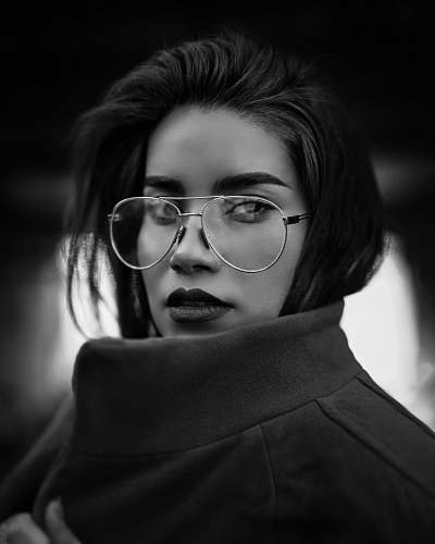 black-and-white grayscale photo of woman wearing coat and eyeglasses portrait