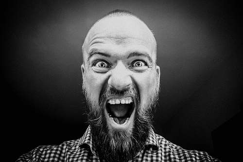 human grayscale photography of man opening his mouth black-and-white