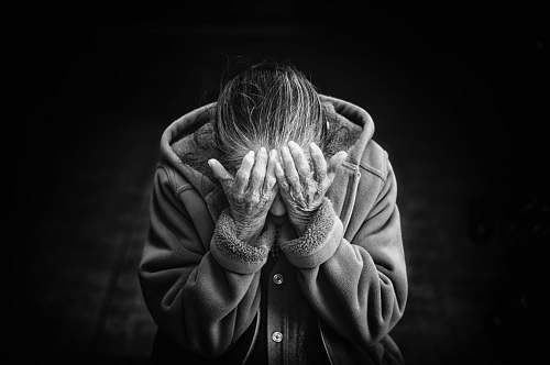 human grayscale photography of person covering face black-and-white