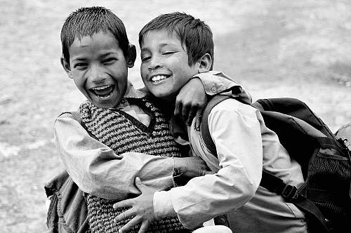 human grayscale photography of two boys hugging while laughing black-and-white