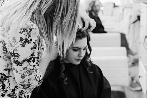 girl grayscale photography of woman getting her hair done inside salon black-and-white