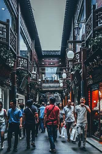person group of people between buildings human