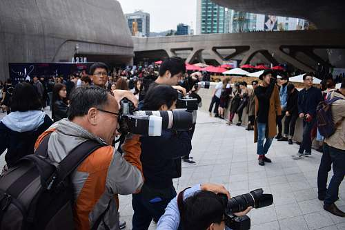 photographer group of photographers holding DSLR cameras in event during daytime crowd