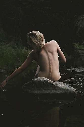 human half naked woman sitting on rock woman