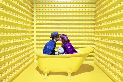 person man and woman kissing inside yellow bathtub human