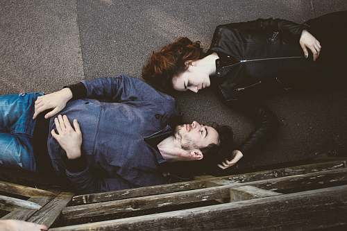 couple man and woman lying on gray concrete surface looking at each other love
