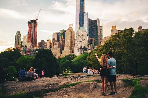 person man and woman standing on hill looking at s skyscraper human