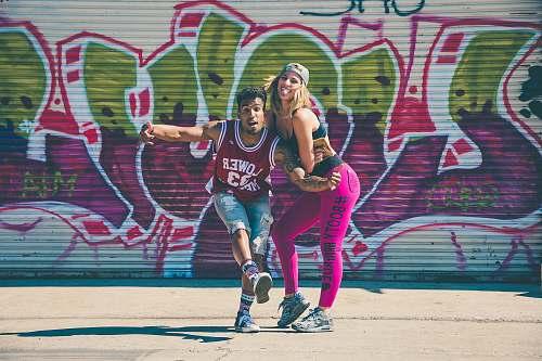 graffiti man beside a woman taking a photo smile