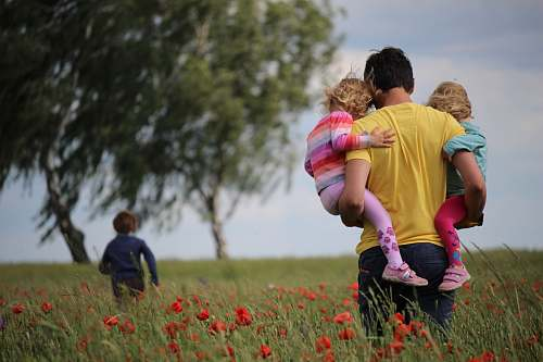 human man carrying to girls on field of red petaled flower family