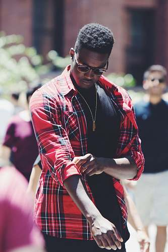 human man fixing his red, black, and white plaid sport shirt sleeve during daytime person