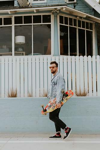 person man holding longboard skateboard