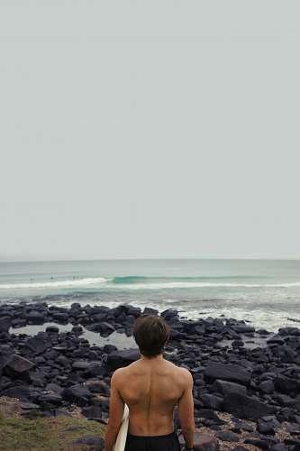 person man holding surfboard near sea back