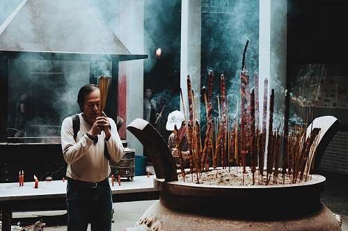 person man in beige long-sleeved shirt in praying gesture incense