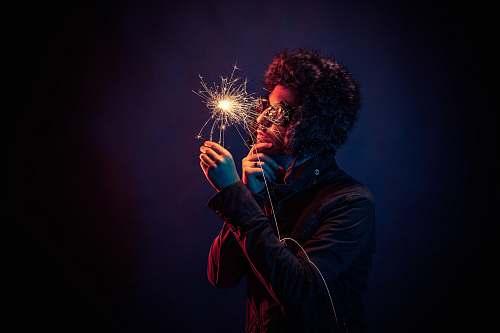 sparkler man in black jacket holding spark man