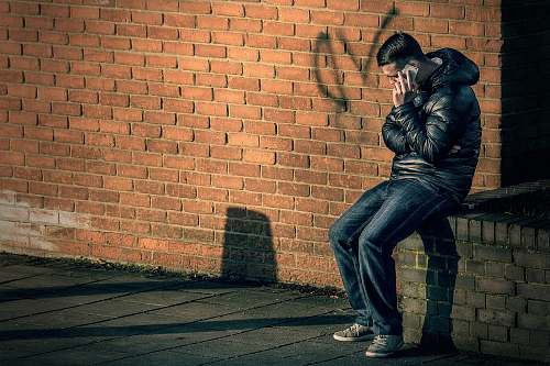 person man in black leather jacket sitting on brick wall holding smartphone human