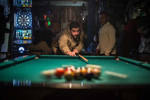 person man in brown jacket playing billiard table