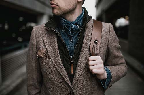 person man in brown suit jacket carrying brown backpack human