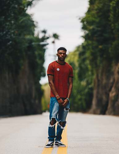 person man in red shirt and blue distress denim jeans standing in middle of road human