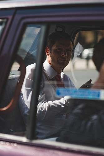 person man in white dress shirt sitting inside vehicle london