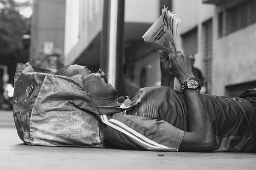 person man lying on sidewalk reading newspaper black-and-white