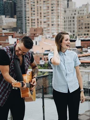 person man playing guitar beside singing woman music