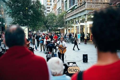 human man playing guitar while singing person