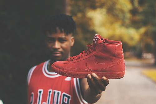 person man showing red Nike high-top sneaker shoe