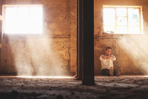 person man sitting beside concrete wall human