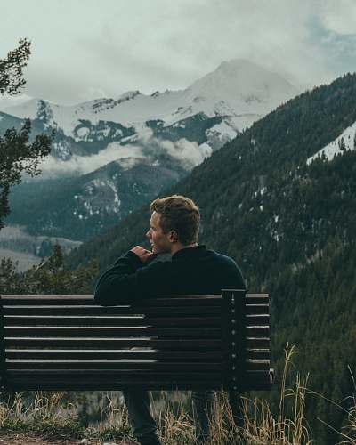 person man sitting on bench on top of the mountain trees