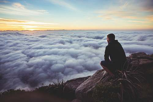 human man sitting on gray rock while staring at white clouds nature