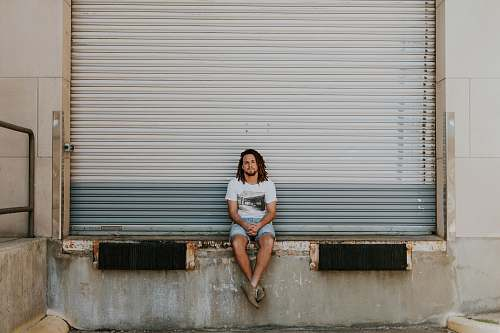 person man sitting on pavement in front of roller shutter human