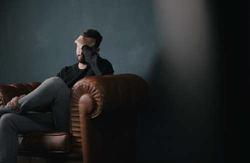 human man sitting on sofa against wall couch