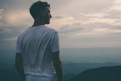 person man standing facing mountains during sunset human