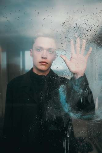 person man standing in front of glass wall while touching it during daytime human