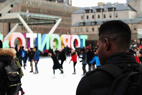toronto man wearing black backpack ice skating with other people near Toronto freestanding decor during daytime crowd