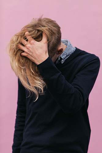 person man wearing black crew-neck sweatshirt with hand running through hair hair