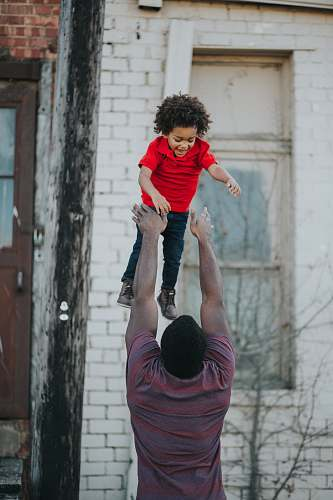 human man wearing purple and red shirt catching child wearing red shirt person