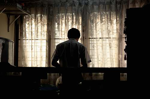 person man wearing white collared shirt near window curtain