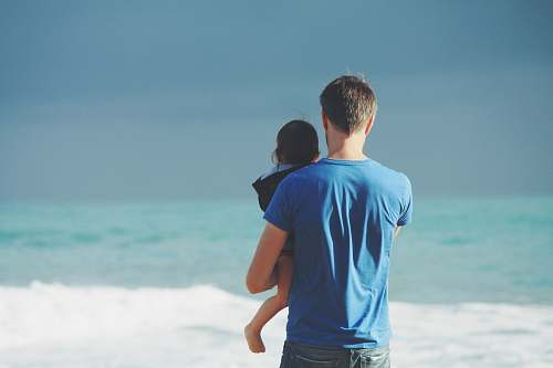 person man wears blue crew-neck t-shirt holding toddler wears black hooded jacket near ocean under blue sky at daytime father