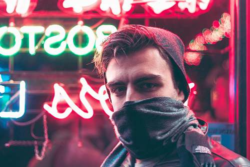 person man with face half covered with mask standing in front of red and green neon light signage during daytime human