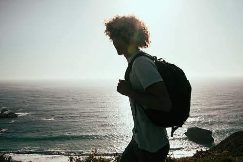 person men wearing white-crew-neck t-shirt and black backpack watching the ocean human