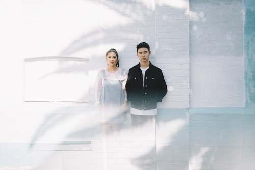 person minimalist photography of man beside woman while leaning against wall human
