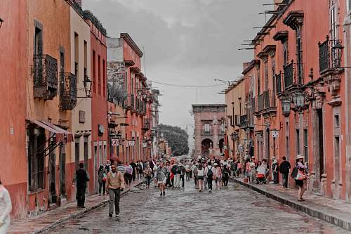 mexico people walking between orange concrete buildings urban