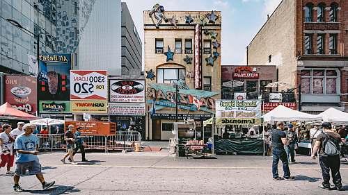 human people walking in street near buildings billboard