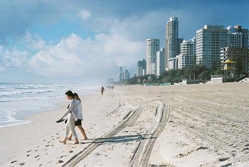 beach people walking on seashore near concrete buildings during daytime sand