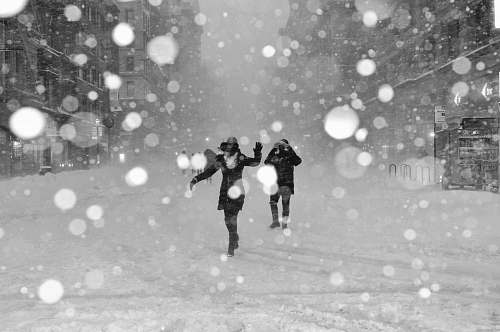 black-and-white people walking on snow covered street with bokeh effects photo winter