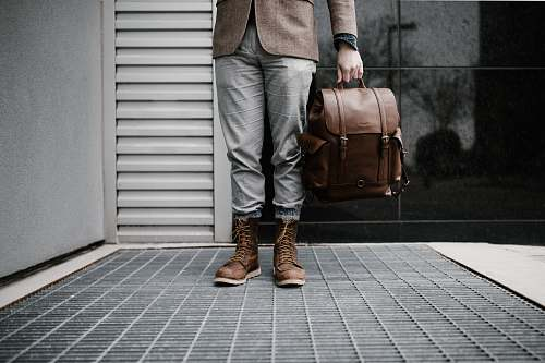boot person holding brown leather bag bag