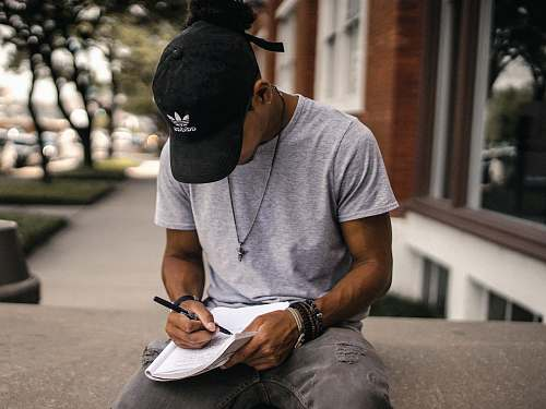 human person in black adidas cap sitting on bench writing on notebook person
