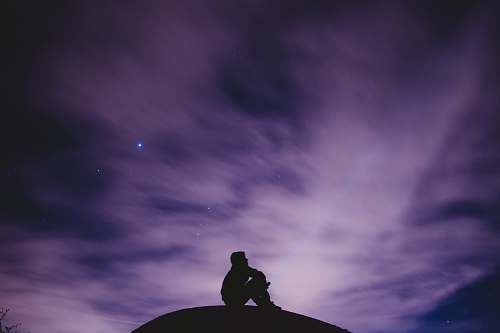 person person sitting on black surface looking to sky silhouette